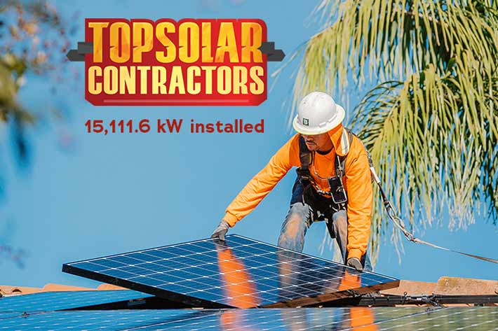 Solar installer placing solar panel on top of roof in San Diego