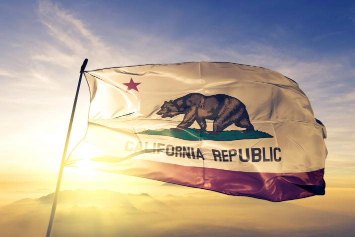 A California state flag waves in a strong wind.